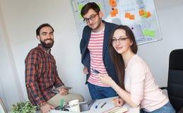 工作在现代办公室的三个同事队  库存照片