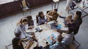 工作在现代办公室的创造性的企业队顶视图  谈话的同事,微笑,高五互相 库存照片