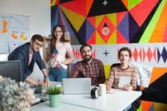 工作在现代办公室的四个同事创造性的队  库存照片