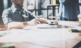 工作在现代办公室的有胡子的工友 供以人员佩带的蓝色衬衣和使用膝上型计算机在木桌 全景视窗 免版税库存照片
