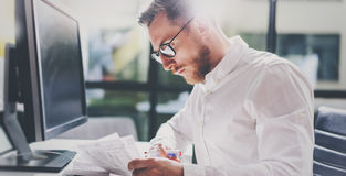 工作在现代办公室的有胡子的年轻商人 供以人员佩带的白色衬衣和关于本文的制造笔记 全景 库存照片