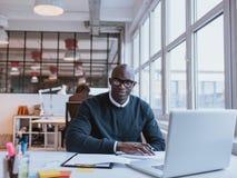 工作在现代办公室的非洲商人 库存图片