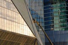 工作在现代商业摩天大楼的高度的建筑工人一艘长平底船的在莫斯科 库存照片
