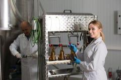工作在现代啤酒厂的妇女 图库摄影