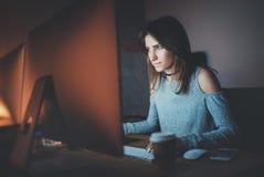 工作在现代演播室办公室的年轻俏丽的妇女在晚上 使用当代台式计算机的女孩,被弄脏 库存照片