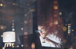 工作在现代顶楼办公室的有胡子的年轻商人在晚上 使用当代笔记本短信的消息的人 图库摄影