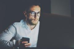 工作在现代顶楼办公室的有胡子的年轻商人在晚上 使用膝上型计算机和smartphope,被弄脏的背景的人 免版税库存照片