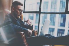 工作在现代顶楼办公室的沉思有胡子的商人 供以人员坐在葡萄酒椅子,举行在有柄小镜  免版税库存照片