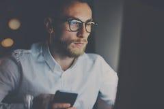 工作在现代顶楼办公室的特写镜头观点的有胡子的年轻商人在晚上 使用膝上型计算机和smartphope的人 免版税图库摄影