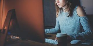 工作在现代顶楼办公室的年轻美丽的妇女在晚上 使用当代台式计算机的女孩,被弄脏 免版税图库摄影