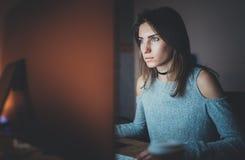 工作在现代顶楼办公室的年轻美丽的妇女在晚上 使用当代台式计算机的女孩,被弄脏 库存图片