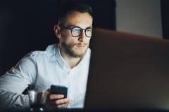 工作在现代顶楼办公室的画象有胡子的商人在晚上 使用当代智能手机的人,被弄脏 免版税库存图片