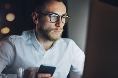 工作在现代顶楼办公室的画象有胡子的商人在晚上 使用当代智能手机的人,被弄脏 免版税图库摄影