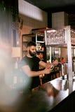 工作在玻璃的酒吧客栈倾吐的啤酒的侍酒者 免版税库存照片