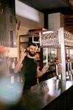 工作在玻璃的酒吧客栈倾吐的啤酒的侍酒者 图库摄影