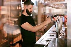 工作在玻璃的酒吧客栈倾吐的啤酒的侍酒者 库存照片
