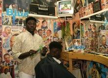 工作在理发店的一个苏丹人难民 免版税图库摄影