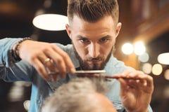 工作在理发店的殷勤年轻理发师 免版税库存图片