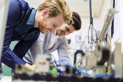 工作在电子组分的两位年轻英俊的工程师 图库摄影
