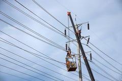 工作在电杆的电工 免版税库存图片