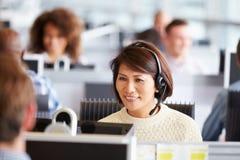工作在电话中心的亚裔妇女,围拢由同事 免版税库存图片