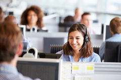 工作在电话中心的少妇,围拢由同事 免版税库存照片