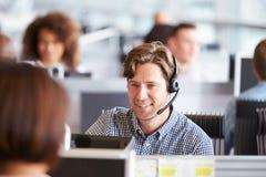 工作在电话中心的年轻人,围拢由同事 免版税库存图片