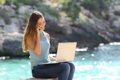 工作在电话的假期的自由职业者的妇女 库存图片