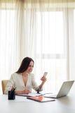 工作在电话的微笑的妇女在现代宽广的办公室 图库摄影