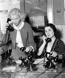 工作在电话银行的两名妇女(所有人被描述不更长生存,并且庄园不存在 供应商保单ther 免版税库存图片