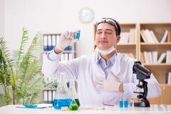 工作在病毒疫苗的实验室的男性医生 免版税图库摄影