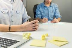 工作在白色现代办公桌的两个人 库存图片