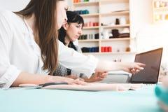 工作在的裁缝缝合演播室 两名妇女裁缝开发和做有现代膝上型计算机的新理念衣物 免版税库存图片