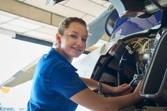 工作在直升机的女性航空工程师画象在飞机棚 免版税图库摄影