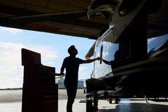 工作在直升机的男性航空工程师剪影在飞机棚 库存照片