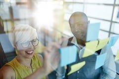 工作在社会媒介战略激发灵感的两个创造性的millenial小企业主使用黏着性笔记  免版税库存照片