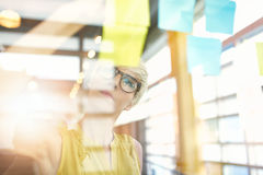 工作在社会媒介战略激发灵感的两个创造性的millenial小企业主使用黏着性笔记  库存照片