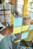 工作在社会媒介战略激发灵感的两个创造性的millenial小企业主使用黏着性笔记  图库摄影
