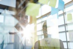 工作在社会媒介战略激发灵感的两个创造性的millenial小企业主使用黏着性笔记  库存图片