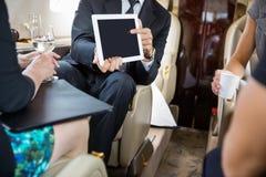 工作在私人喷气式飞机的商务伙伴 免版税图库摄影