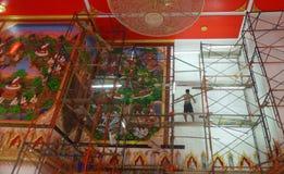 工作在空的佛教寺庙墙壁上的艺术家 图库摄影