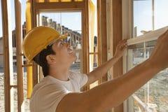 工作在窗口的建筑工人 图库摄影