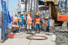 工作在站点桥梁打桩的建筑工人 免版税库存图片