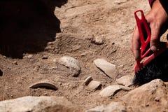 工作在站点,有刷子的手的考古学家 免版税库存图片