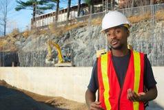 工作在站点,白色盔甲的年轻建筑工人工头 免版税库存图片