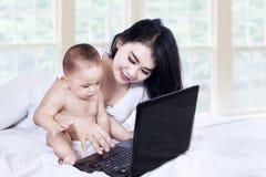 工作在笔记本的妈妈和婴孩 免版税库存照片