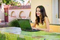 工作在笔记本的愉快的微笑的女孩,当坐在家庭雀鳝时 免版税库存照片