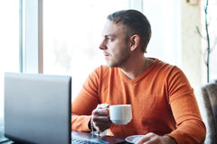 工作在笔记本,认为的英俊的年轻人,看窗口,当享用在咖啡馆时的咖啡 免版税库存照片