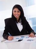 工作在纸的女实业家 免版税库存图片