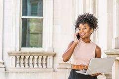 工作在纽约的非裔美国人的女实业家 有非洲的发型的年轻黑人大学生坐在葡萄酒的栏杆 免版税图库摄影